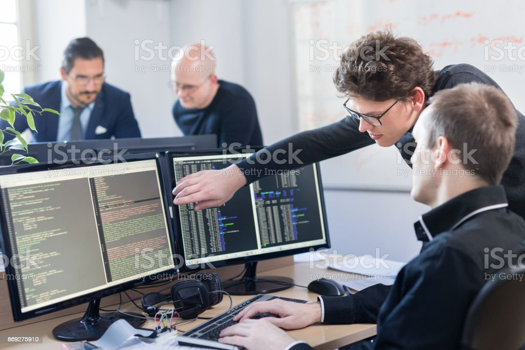 Startup business problem solving. Software developers working on desktop computer. stock photo