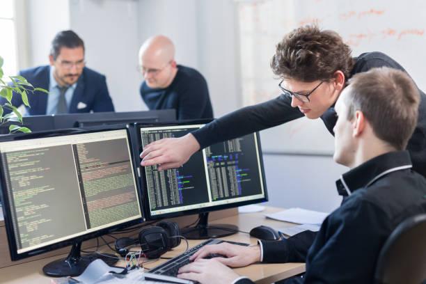Startup business problem solving. Software developers working on desktop computer. stock photo