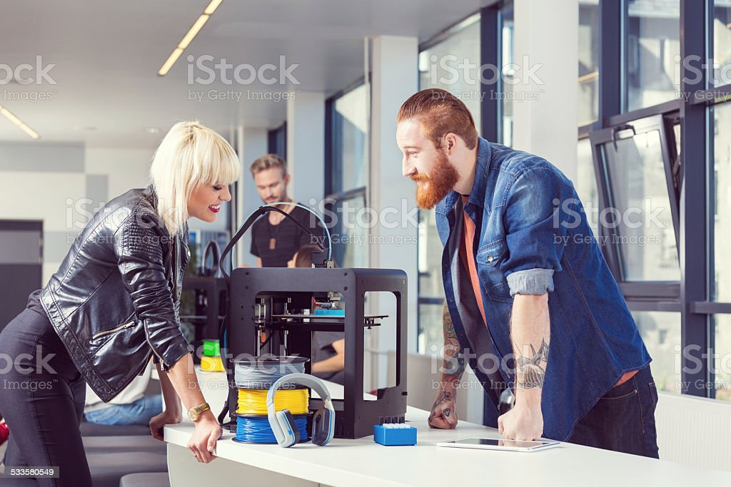 Start-up business team in 3D printer office Bearded man with tatoos using a 3D printer in an office with his coworker. 2015 Stock Photo