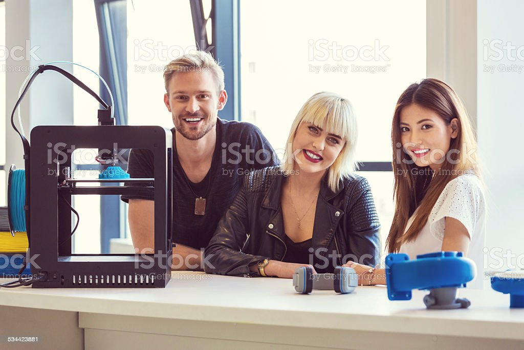 Start-up Business Team in 3D printer office Multi ethnic start-up business team working together in the 3D printer office, smiling at camera. 2015 Stock Photo