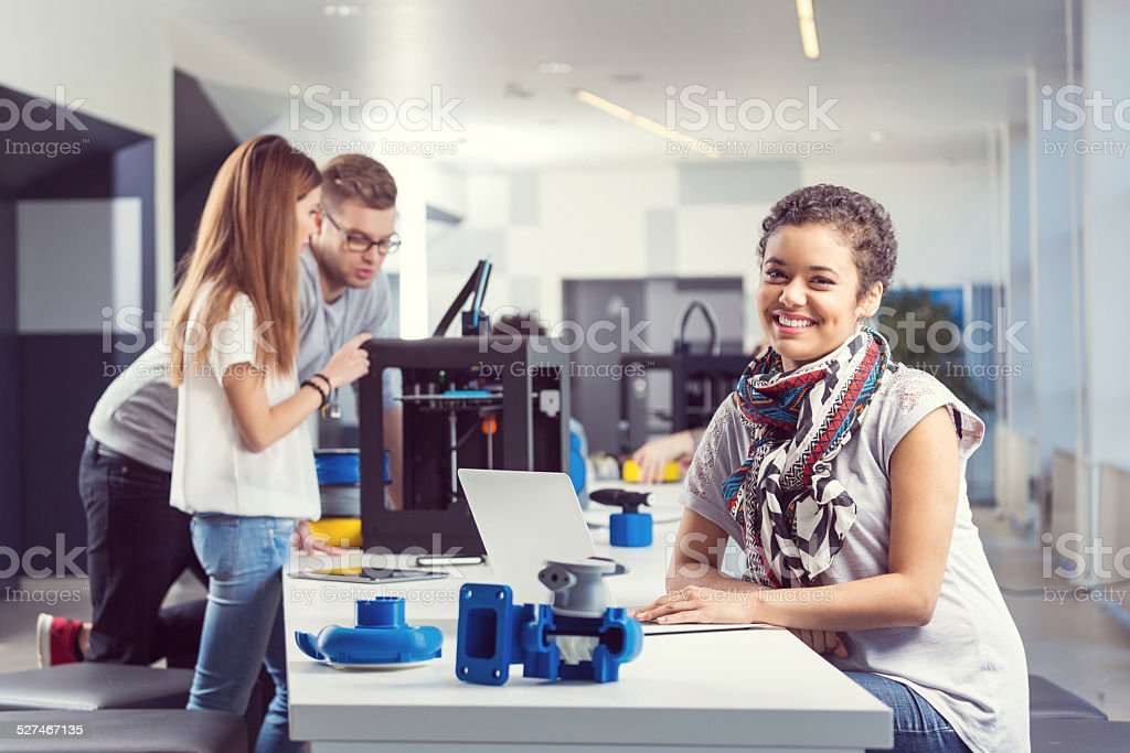 Start-up Business Team in the office Smiling mixed race young woman working on laptop in the office while her coworkers using 3D printer. 3D Printing Stock Photo