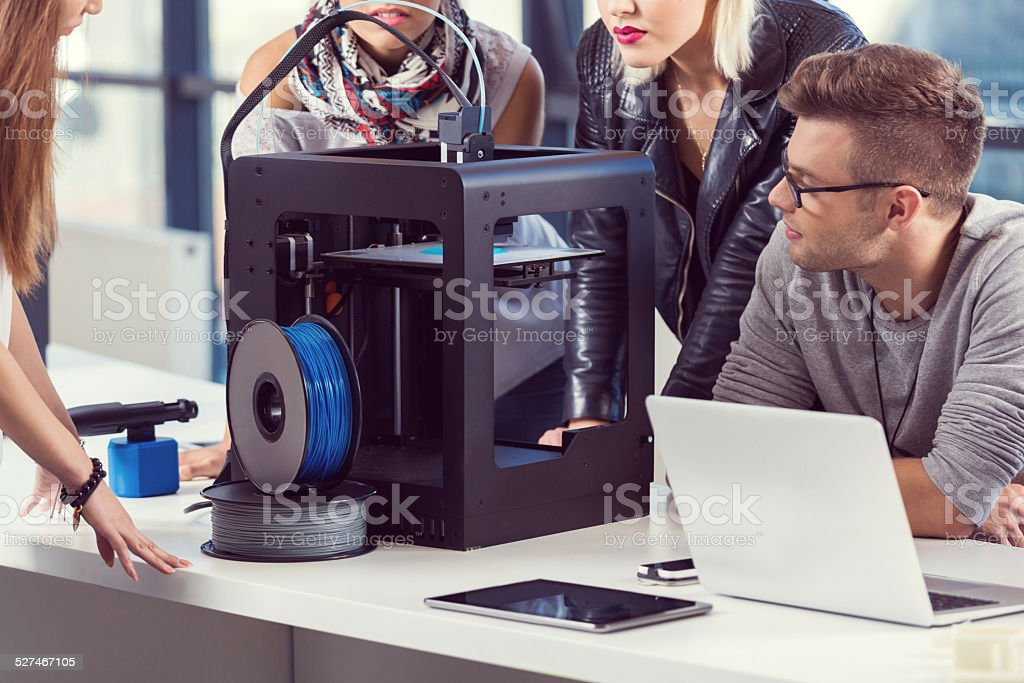 Start-up Business Team working by 3D printer Start-up business team working together in the office, using a 3D printer.  3D Printing Stock Photo