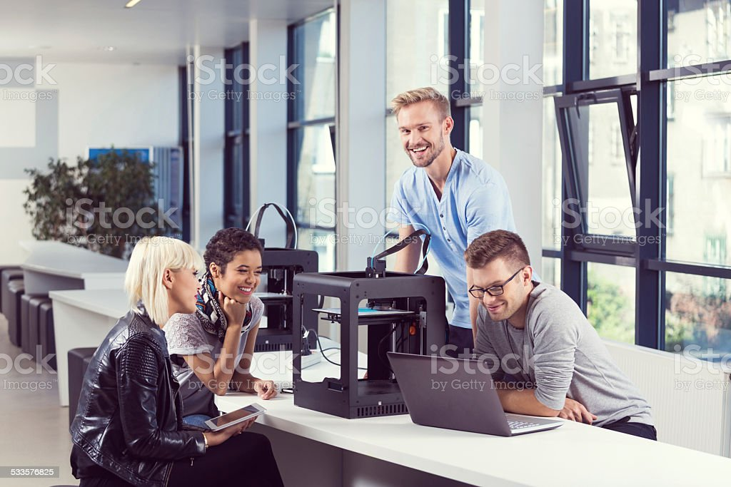 Start-up Business Team working by 3D printer Start-up business team working together in the office, using a 3D printers and computer. 2015 Stock Photo