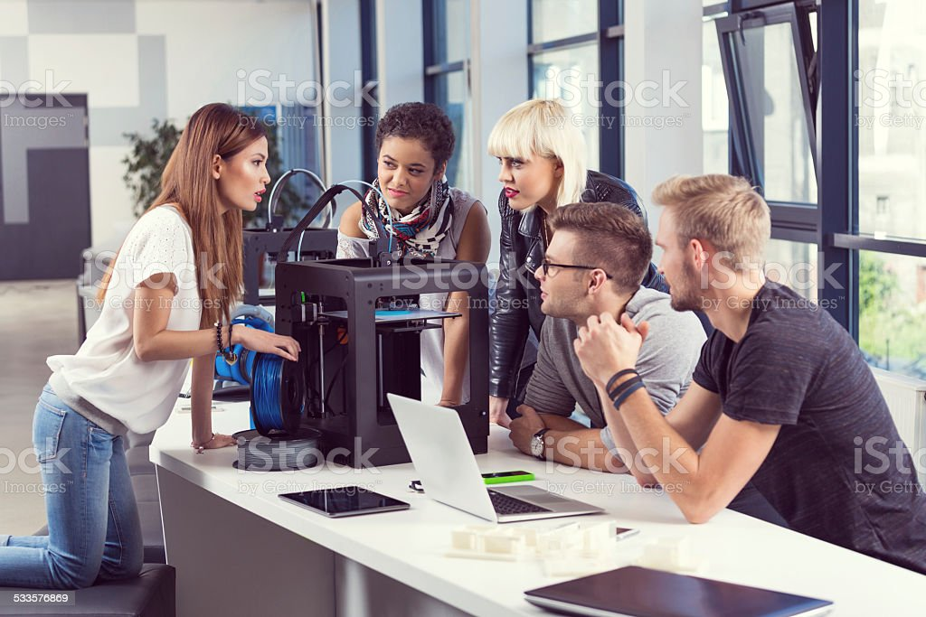 Start-up Business Team working by 3D printer Start-up business team working together in the office, using a 3D printer and computer. 2015 Stock Photo