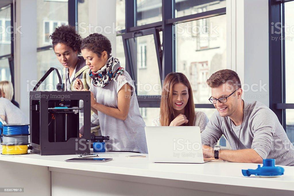 Start-up Business Team working in 3D printer office Start-up business team working together in the 3D printer office, using 3D printer and laptop. 2015 Stock Photo