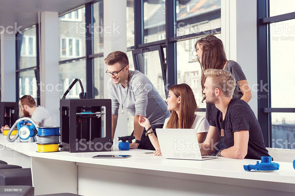 Start-up Business Team working in 3D printer office Start-up business team working together in the 3D printer office, using 3D printer and laptop. 2015 Stock Photo