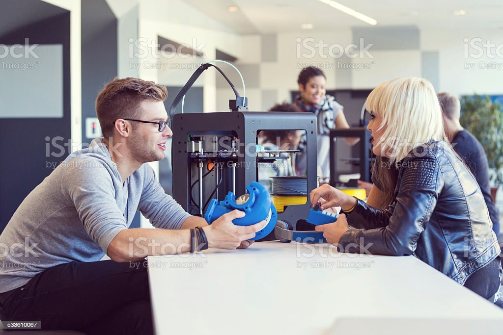 Start-up Business Team working in 3D printer office Start-up business team working together in the 3D printer office, watching printouts and talking. 2015 Stock Photo