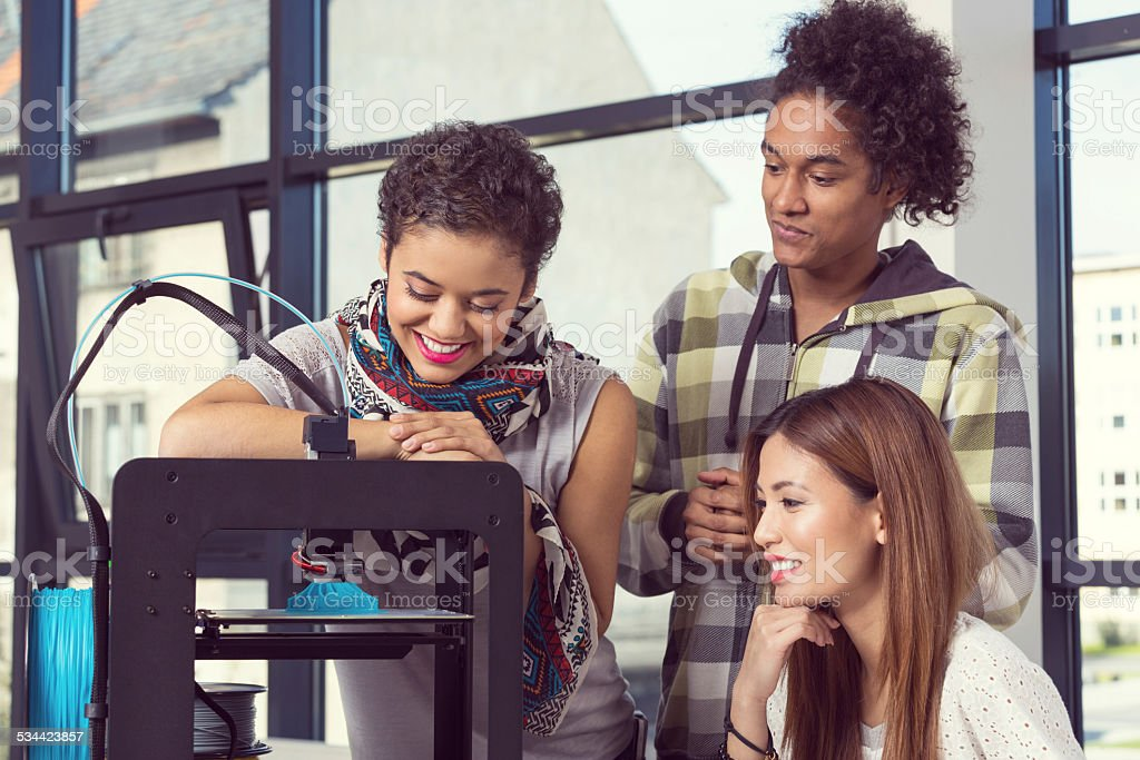 Start-up Business Team working in 3D printer office Multi ethnic start-up business team working together in the 3D printer office, watching at 3D prinout. 2015 Stock Photo