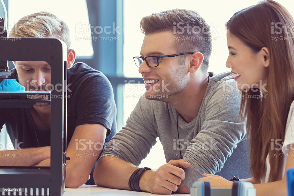 Start-up Business Team working in 3D printer office Start-up business team working together in the 3D printer office, watching at 3D prinout. Close up of faces. 2015 Stock Photo