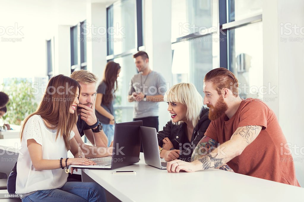 Start-up business team working together on laptops Start-up business team brainstorming, working together on computers in an office with people talking in the background. 2015 Stock Photo