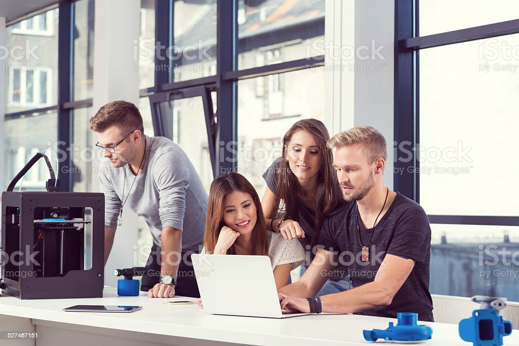 Start-up Business Team working together Start-up business team working together on the laptop, man wearing glasses using 3D printer. 3D Printing Stock Photo