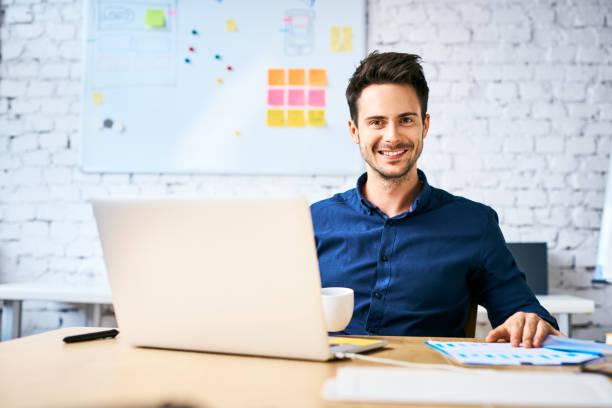 Startup Geschäftsmann sitzt am Schreibtisch mit Blick auf die Kamera beim Kaffeetrinken und die Arbeit mit Laptop und Notizen – Foto