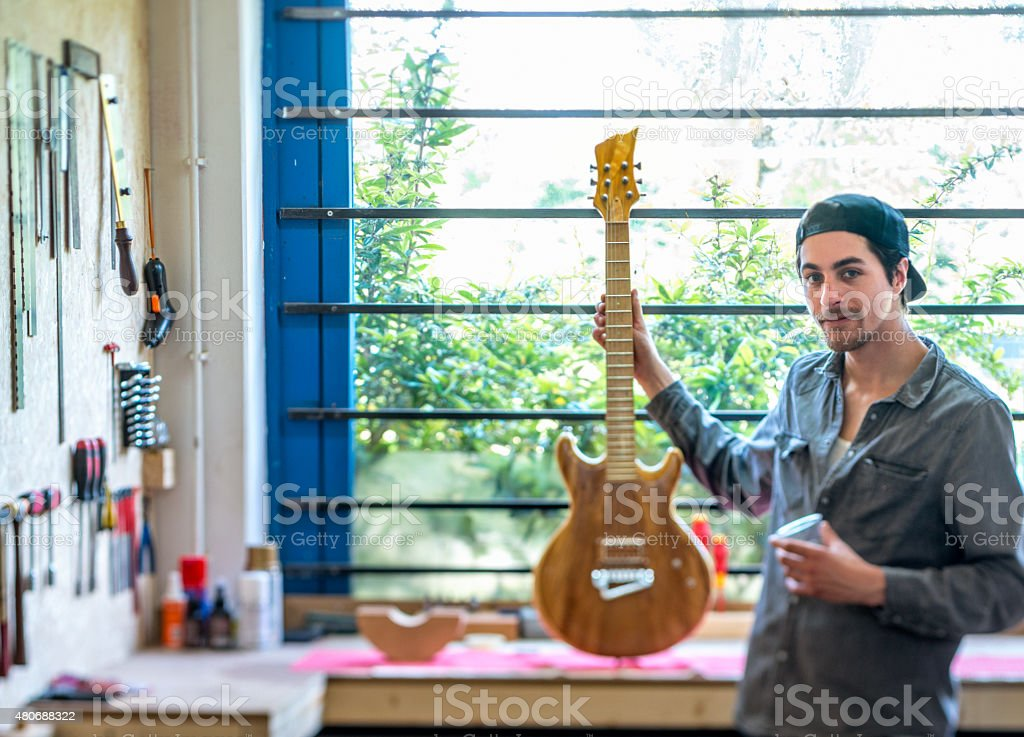Startup, man  Building Guitar in his Workshop stock photo