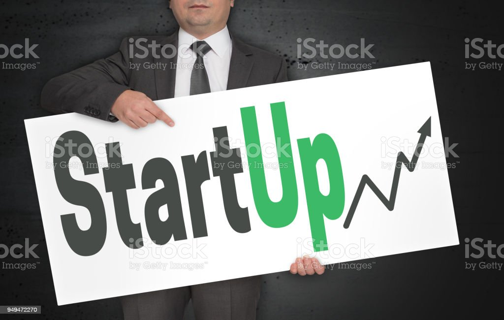 StartUp poster is held by businessman stock photo