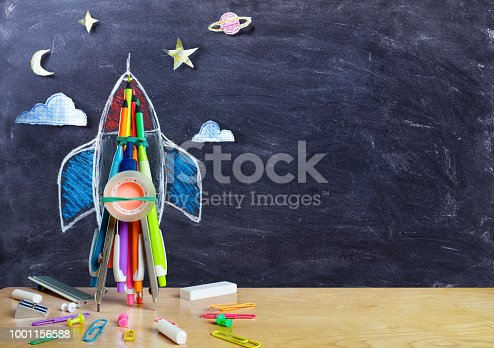istock Startup - Rocket Drawing With School Supplies On Table 1001156588
