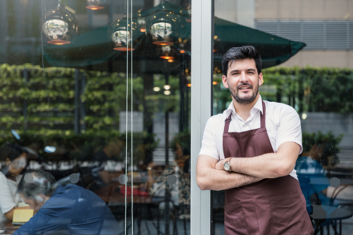 Startup successful small business owner man walking in his coffee shop or restaurant.