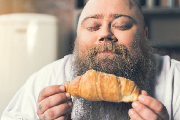 hungernde fetter kerl duft von gebäck zu genießen - geschlossene küchen stock-fotos und bilder