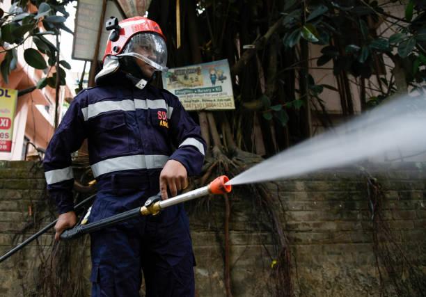 Mitarbeiter der State Disaster Response Force sprühen Desinfektionsmittel in einem Wohngebiet – Foto