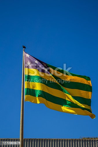 Bandeira do estado de Goiás hasteada tremulando ao vento e com céu azul ao fundo.