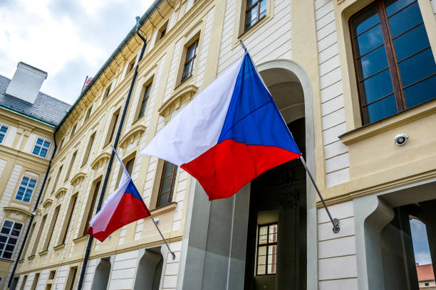 state flags of the czech republic at the entrance to the building of the president of the czech republic - чехия стоковые фото и изображения