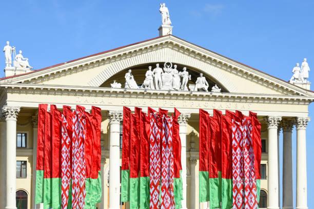 flagi państwowe republiki białoruś na tle pałacu kultury związków zawodowych w mińsku - białoruś zdjęcia i obrazy z banku zdjęć