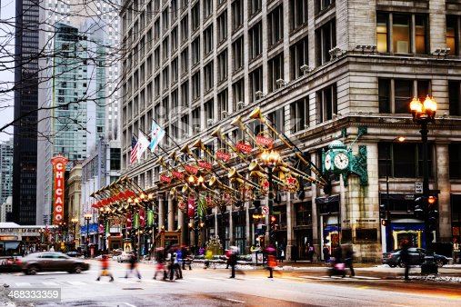 Chicago, USA - January 4, 2014: Macy's Department Store (former Marshall Fields) on State Street  with christmas decorations, in The Loop, downtown Chicago. Motion blurred background people and cars. Winter scene with snow.