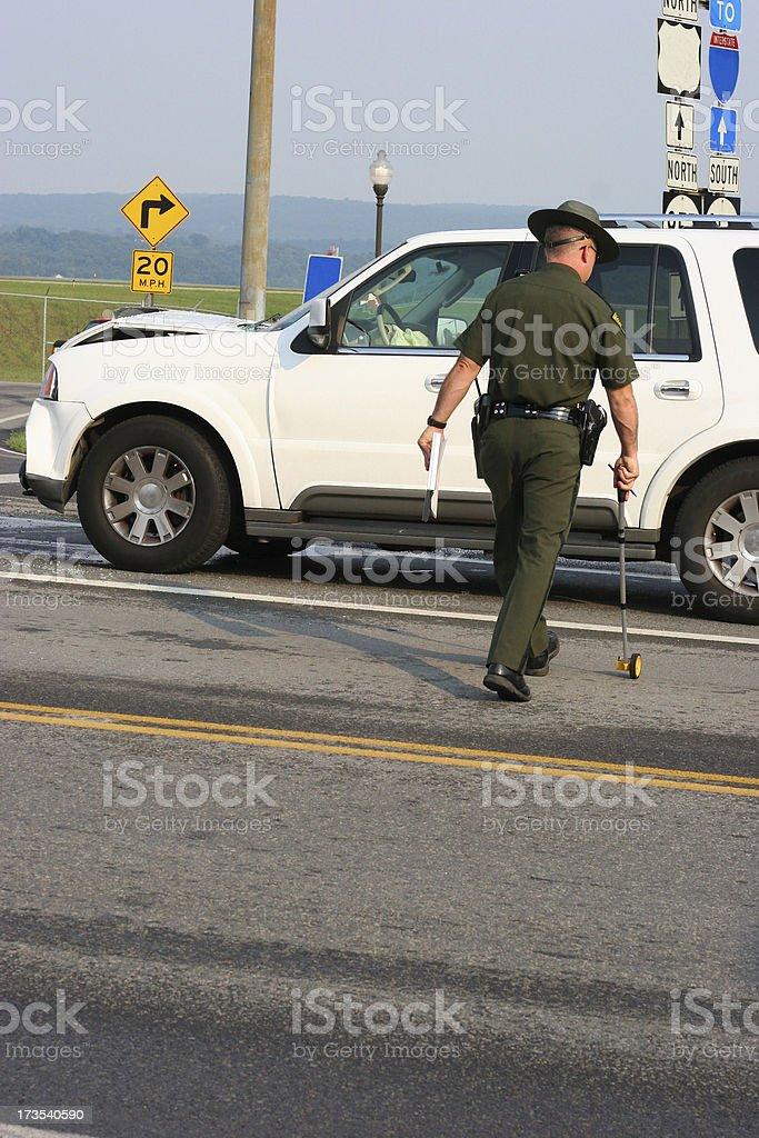 State Trooper Measuring Accident Scene stock photo