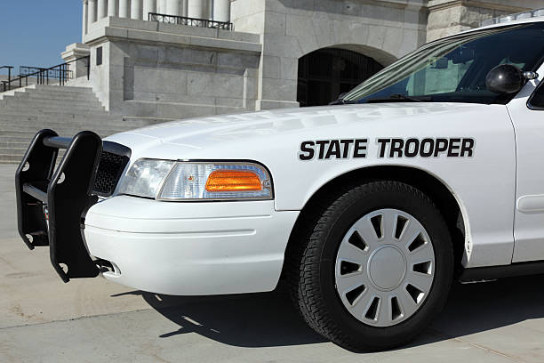 State Trooper Police Car in front of Office Capitol Building DSLR picture of a white state trooper police car in front of an office building. The sky is blue without a cloud.  trooper stock pictures, royalty-free photos & images