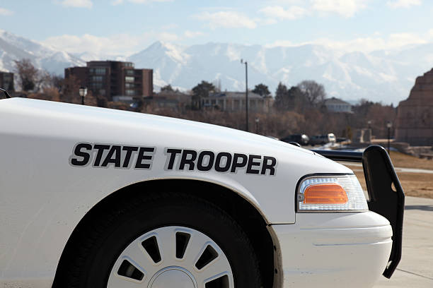 State Trooper Police Car in front of Office Capitol Building DSLR picture of a white state trooper police car in front of an office building. The sky is blue with few clouds and there is city buildings and mountains in the background. trooper stock pictures, royalty-free photos & images
