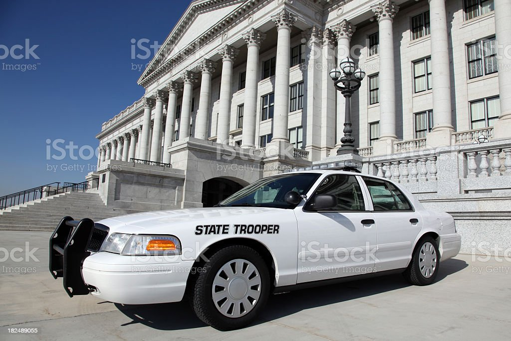 DSLR picture of a white state trooper police car in front of an...