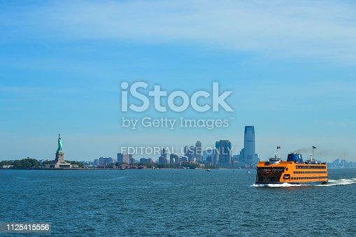 New York, NY - June 30, 2014: Staten Island Ferry crossing the New York Bay, with views of the Statue of Liberty and the New York City skyline on a summer day