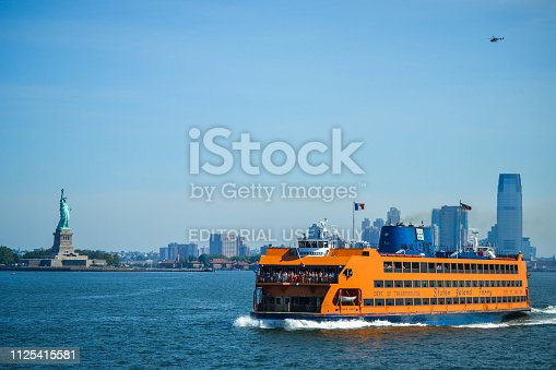 New York, NY - June 30, 2018: Staten Island Ferry crossing the New York Bay, with views of the Statue of Liberty and the New York City skyline on a summer day