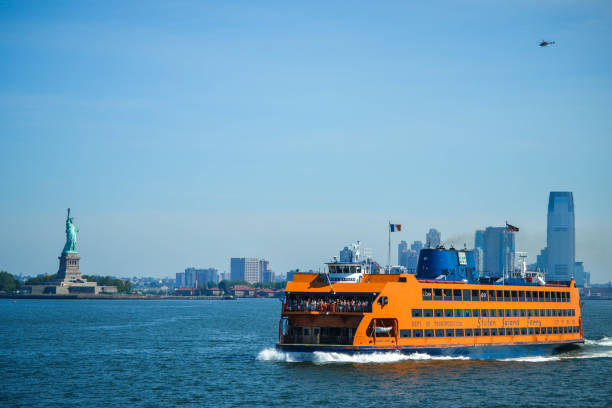 Staten Island Ferry crossing the New York Bay, with views of the Statue of Liberty and the New York City skyline on a summer day New York, NY - June 30, 2018: Staten Island Ferry crossing the New York Bay, with views of the Statue of Liberty and the New York City skyline on a summer day liberty island stock pictures, royalty-free photos & images
