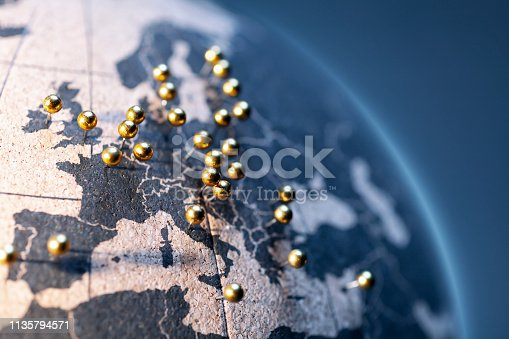States and capitals of the European Union pinned with golden pins on a cork globe.