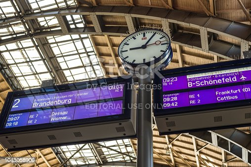 Berlin, Germany - May 28, 2017: Clock and train departure timetable display in a railway station in Berlin, Germany.