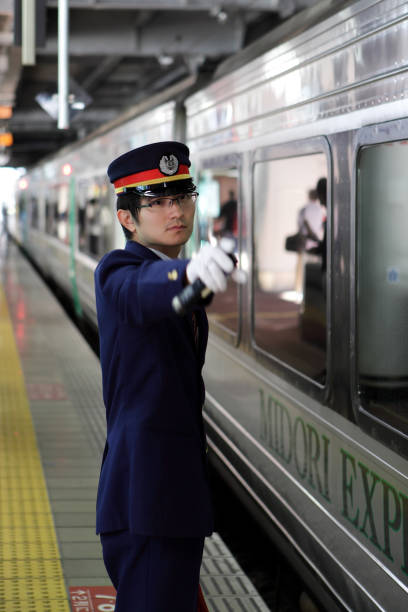 station employee giving a signal for departure - transport conductor stock photos and pictures