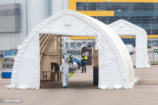 Vilnius, Lithuania - October 5 2020: Paramedic wearing protective equipment disinfecting mobile testing station tent for cars during Coronavirus or COVID19 outbreak, medical hotspot