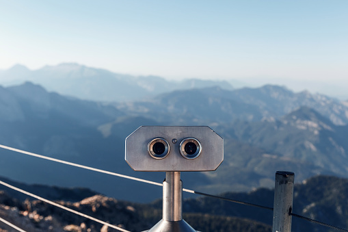Stationary binoculars or binoscope on the viewing platform against the background beautiful landscape in the mountains. Lovely view of the Taurus Mountains and the Mediterranean coast. Kemer, Turkey