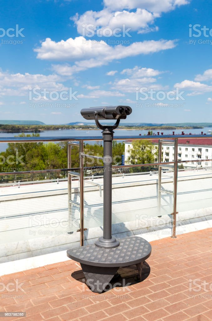 Stationary tourist telescope at the city embankment in summer day stock photo