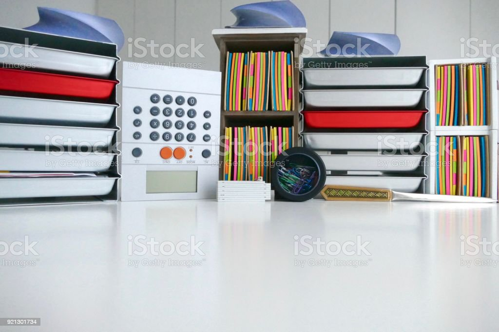 Stationery boxes and colorful adhesives notes in a row, on a white table stock photo