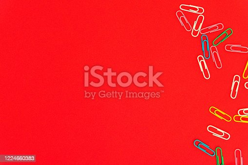 istock Stationery colorful paper clips chaotically scattered and made frame on red background. 1224660383