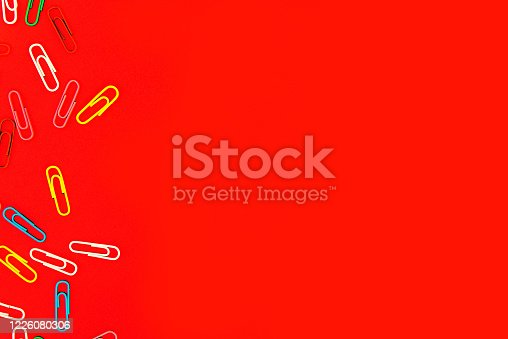 istock Stationery colorful paper clips chaotically scattered and made frame on red background. 1226080306