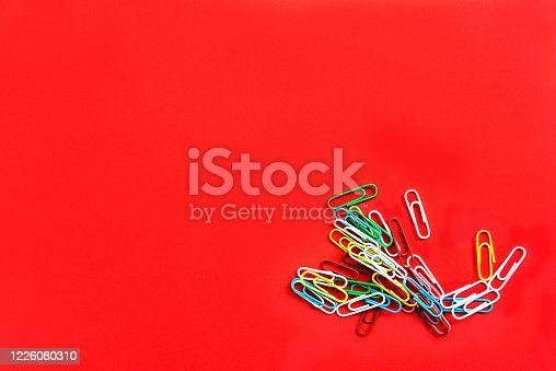 istock Stationery colorful paper clips chaotically scattered on red background. 1226080310
