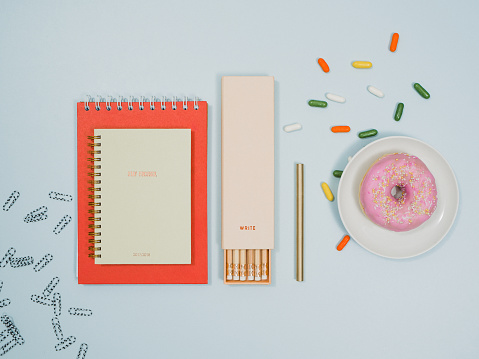 Stationery from above with notebook pencils and donut