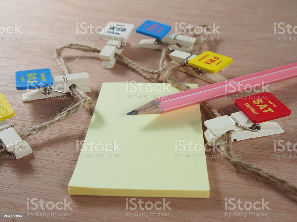 Stationery, pink pencil, sticky paper with wooden clips stock photo
