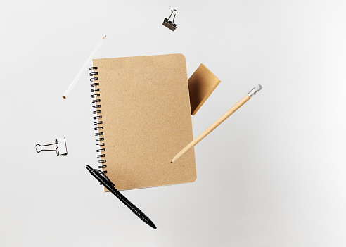 Stationery set. Levitation of notepad, pencils, pen, sticker and binder clips. Copy space on notebook and notes. Writing tools. Office supplies. Isolated on gray backdrop.