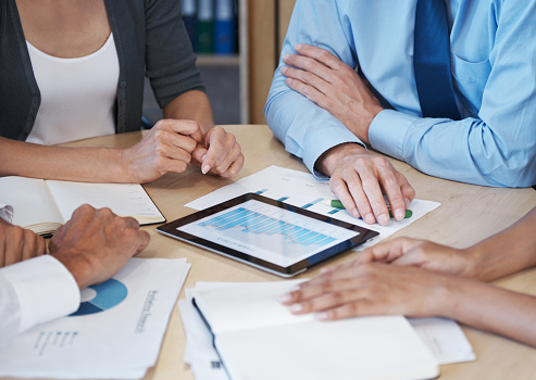 Cropped shot of a group of business people using a digital tablet to analyze their statistics