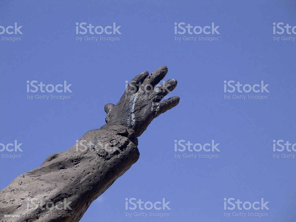 Statue arm reaching for sky, royalty-free stock photo