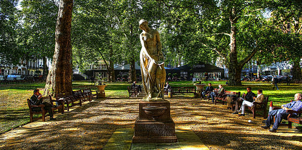 Statue in Berkeley Square London, United Kingdom - September 17, 2012: HDR image of Nymph statue by Alexander Munro, Berkeley Square (1858) with people sitting on benches during their lunch break.  mayfair stock pictures, royalty-free photos & images