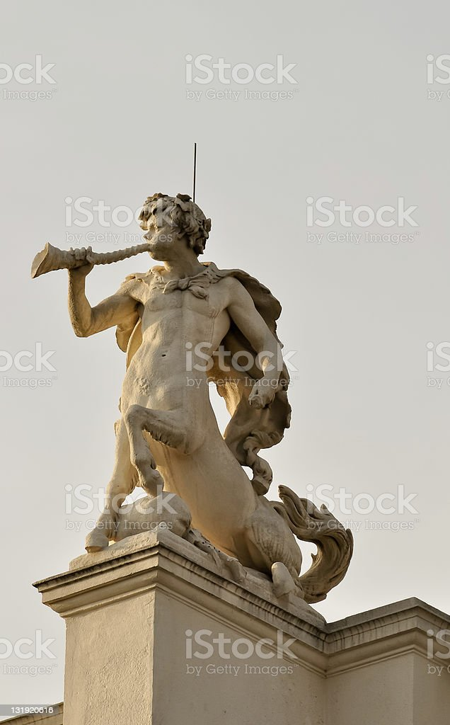 statue of a centaur blowing his horn atop historical building stock photo